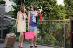 获得秀丽的妇女拿着与行李和步行的乐趣购物袋在购物中心附近 免版税图库摄影
