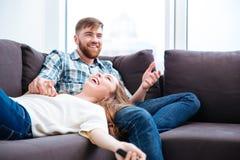 获得笑的夫妇在沙发的乐趣 免版税库存图片