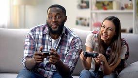 获得笑的mixed-race的家庭乐趣,在家打电子游戏,悠闲时间 库存照片