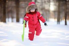 获得红色冬天的衣裳的小男孩与新鲜的雪的乐趣 免版税库存照片