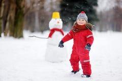 获得红色冬天的衣裳的小男孩与雪人的乐趣 库存照片