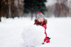 获得红色冬天的衣裳的小男孩与雪人的乐趣 免版税图库摄影