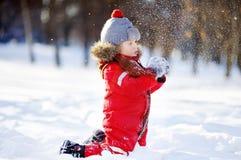 获得红色冬天的衣裳的小男孩与雪的乐趣 免版税库存照片