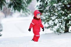 获得红色冬天的衣裳的逗人喜爱的小男孩与雪的乐趣 免版税库存图片