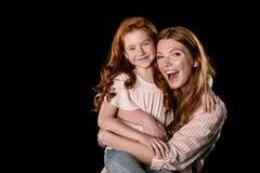 获得红头发人的母亲和的女儿在黑色一起隔绝的乐趣 免版税库存照片