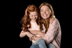 获得红头发人的母亲和的女儿在黑色一起隔绝的乐趣 库存照片