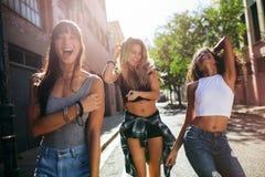 获得美丽的女孩走在城市附近和乐趣 免版税图库摄影