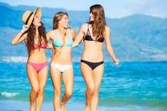 获得美丽的女孩走在海滩的乐趣 图库摄影