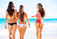 获得美丽的女孩走在海滩的乐趣 免版税库存图片