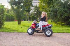 获得美丽的小女孩在她的玩具自行车的乐趣 库存照片