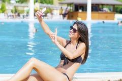 获得美丽的年轻微笑的妇女做selfie的乐趣 免版税库存图片