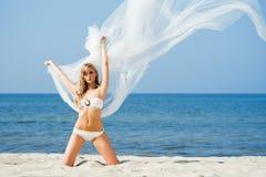 获得美丽,适合的妇女与丝绸的乐趣在一个有风海滩 库存照片