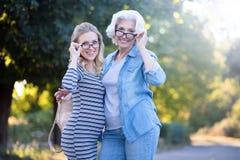获得老化的妇女与怀孕的女儿的乐趣户外 免版税库存照片