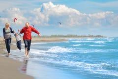 获得观点的愉快的年轻的家庭在海滩的乐趣 免版税库存图片