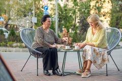 获得资深的妇女坐在街道咖啡馆,饮用的咖啡,谈,笑和乐趣 退休的愉快的人 库存图片