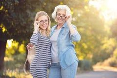 获得退休的妇女与年轻怀孕的女儿的乐趣户外 免版税图库摄影