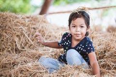 获得逗人喜爱的亚裔儿童的女孩乐趣使用与干草堆 免版税图库摄影