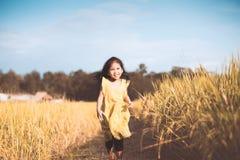 获得逗人喜爱的亚裔儿童的女孩乐趣跑在稻田 免版税库存图片