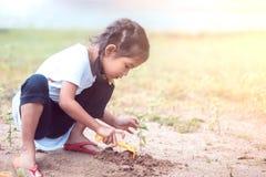 获得逗人喜爱的亚裔小孩的女孩乐趣使用与沙子 库存照片