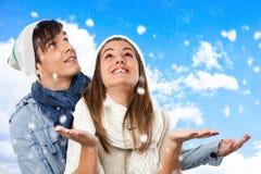 获得逗人喜爱的冬天的夫妇与雪的乐趣。 图库摄影