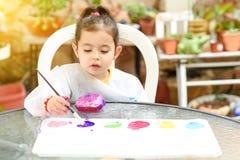 获得逗人喜爱的女孩乐趣,上色与刷子,使用和绘 有油漆的学龄前儿童在庭院 免版税库存图片