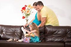 获得逗人喜爱的小女孩与礼物的乐趣 免版税库存图片