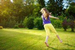 获得逗人喜爱的小女孩在一棵草的乐趣在后院在晴朗的夏天晚上 免版税图库摄影