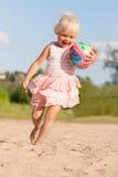 获得逗人喜爱的小女孩在海滩的乐趣 图库摄影