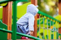获得逗人喜爱的小孩的女孩在户外操场的乐趣 库存图片