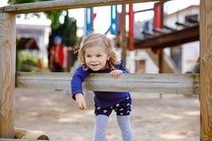 获得逗人喜爱的小孩的女孩在操场的乐趣 上升,摇摆和滑在不同的愉快的健康小孩 免版税库存图片