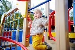 获得逗人喜爱的小孩的男孩在户外操场的乐趣 图库摄影
