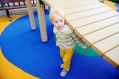 获得逗人喜爱的小孩的男孩在操场的乐趣 库存图片