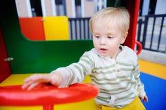 获得逗人喜爱的小孩的男孩在操场的乐趣 免版税图库摄影