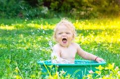 获得逗人喜爱的小小孩的女孩乐趣用水 免版税图库摄影