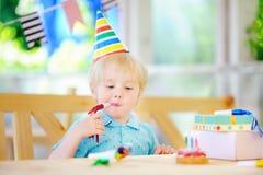 获得逗人喜爱的小男孩乐趣和庆祝与五颜六色的装饰的生日聚会并且结块 库存照片