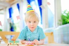 获得逗人喜爱的小男孩乐趣和庆祝与五颜六色的装饰的生日聚会并且结块 免版税库存照片