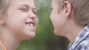 获得逗人喜爱的男孩和俏丽的女孩接近的画象坐在公园,设法磨擦他们的鼻子和乐趣 两三 股票视频