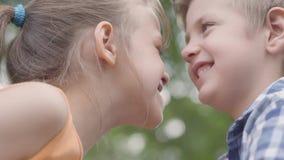 获得逗人喜爱的男孩和的女孩的接近的面孔坐在公园,设法磨擦他们的鼻子和乐趣 两三愉快 股票视频