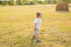 获得逗人喜爱的矮小的男婴画象乐趣外面 使用微笑的愉快的孩子户外 库存照片