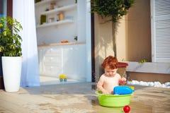 获得逗人喜爱的红头发人小孩的婴孩乐趣用在夏天大阳台的水 免版税库存图片