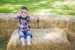 获得逗人喜爱的年轻混合的族种的男孩在干草捆的乐趣 免版税库存图片