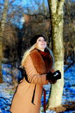 获得雪的女孩冬天乐趣,做雪球 免版税库存图片