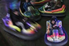 获得青少年的男孩乐趣驾驶一辆碰撞用汽车在游乐园,行动迷离图象 图库摄影