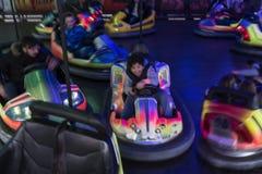 获得青少年的男孩乐趣驾驶一辆碰撞用汽车在游乐园,行动迷离图象 库存图片