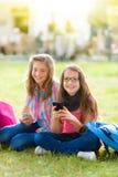 获得青少年的女小学生与手机的乐趣 免版税库存图片