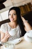 获得饮用的咖啡或茶美丽的性感的深色的女孩的少妇画象轻轻地微笑和看照相机的乐趣 库存图片