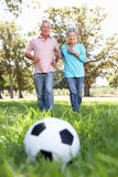 获得高级的夫妇乐趣踢橄榄球 库存图片