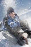获得年轻的人与雪撬的乐趣 库存图片
