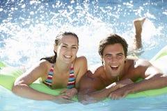 获得年轻的夫妇与可膨胀的Airbed游泳池的乐趣一起 免版税库存照片