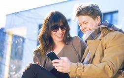 获得年轻的夫妇与手机的乐趣 免版税图库摄影